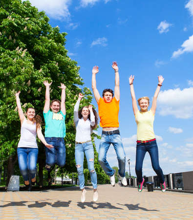 Group of smiling teenagers jumping outdoors. Friendship concept photo