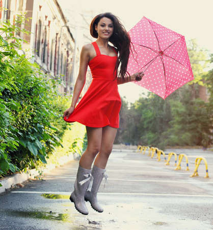 Portrait of beautiful young girl jumping with umbrella under rain photo