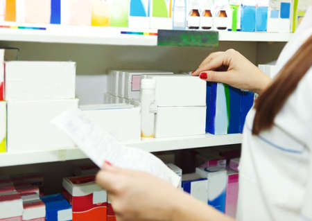 inventory: Pharmacist chemist woman with prescription in a drugstore. Close up