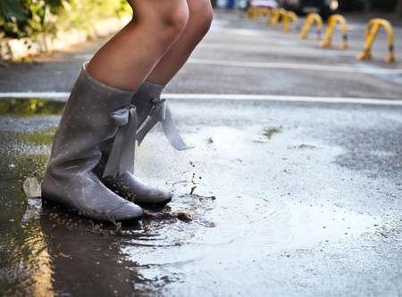 Woman wearing grey polka dots rain boots jumping into a puddle. Close up