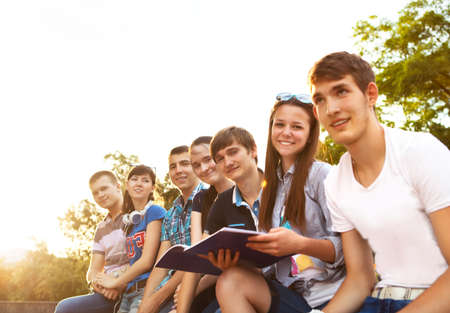 school friends: Group of students or teenagers with notebooks outdoors in summer evening