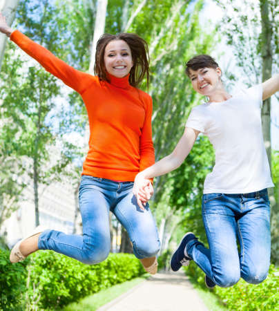 Happy young teen girls jumping it the park on beautiful spring day photo