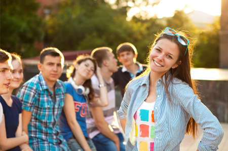 uni: Female smiling student outdoors in the evening with friends
