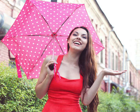 Portrait of beautiful young girl walking with umbrella under the rain photo