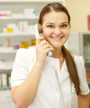 Portrait of a smiling female pharmacist on the phone at drugstore photo