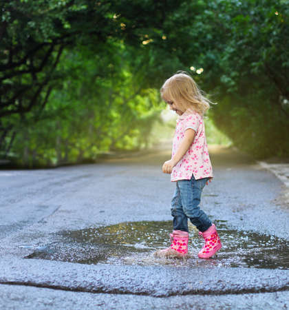 puddle: Cute little girl wearing rain boots jumping into a puddle