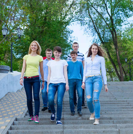 freshmen: Group of smiling teenagers walking outdoors. Friendship concept