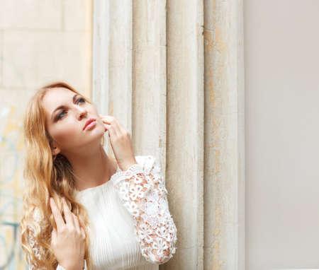 Portrait of a beautiful blond woman in beige long dress outdoors photo