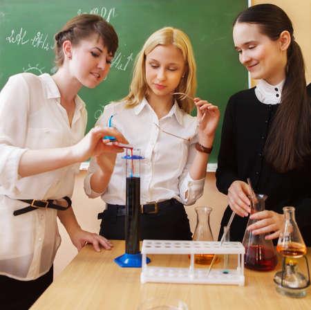 교실에서 액체 공식으로 화학 실험실에서 근무하는 여자