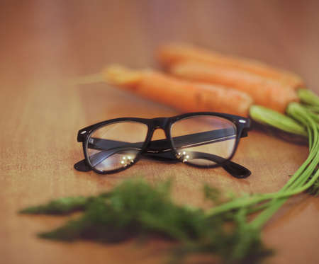 eyesight: Glasses next to a carrot on the wooden background. Retro toned image Stock Photo
