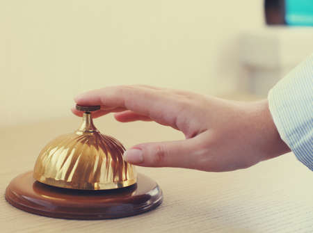 Hand of a woman using a hotel bell in retro style photo