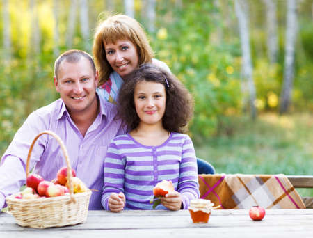 Happy young family with daughter on autumn picnic photo