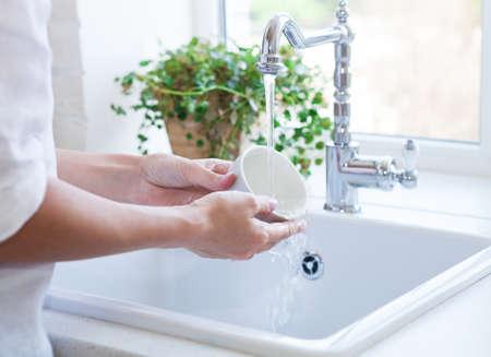 lavar trastes: Mujer para la vajilla en el fregadero. De cerca