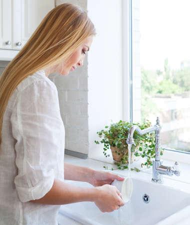 lavar trastes: Mujer que hace la colada en la cocina Foto de archivo
