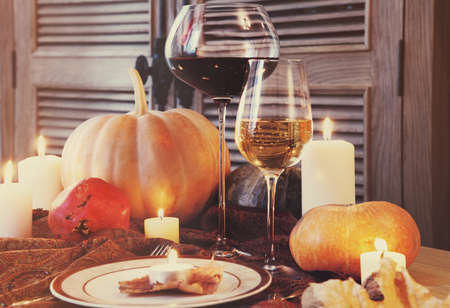 Autumn place setting. Thanksgiving dinner. Fall season fruit, pumpkins, plates, wine and candles. Thanksgiving dinner