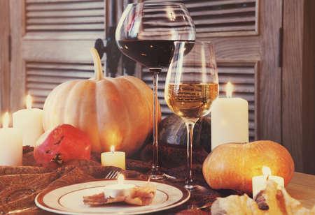 candle light table setting: Autumn place setting. Thanksgiving dinner. Fall season fruit, pumpkins, plates, wine and candles. Thanksgiving dinner
