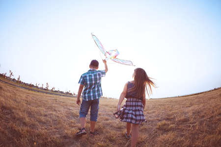 Happy boy and little girl running with bright kite on a meadow in a sunny evening photo