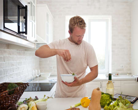 and the horizontal man: Handsome man cooking at home preparing salad in kitchen Stock Photo