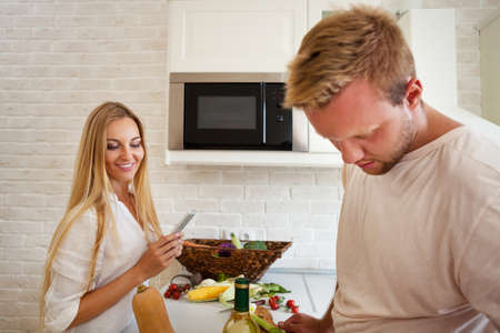 Portrait of happy young couple cutting vegetables at the kitchen  photo