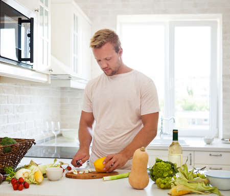 Handsome young man cooking at home preparing salad in kitchen Stock Photo