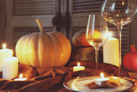 Autumn place setting. Thanksgiving dinner. Fall season fruit, pumpkins, plates, wine and candles. Thanksgiving dinner photo