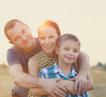Familia joven feliz con el pequeño hijo al aire libre