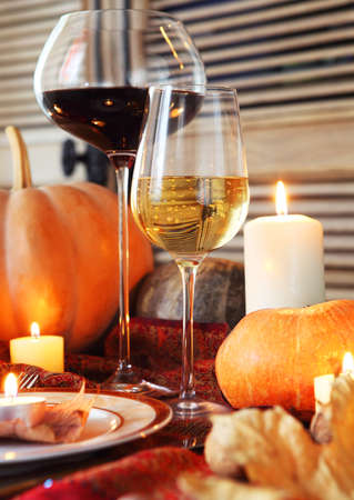 table decorations: Autumn place setting. Thanksgiving dinner. Fall season fruit, pumpkins, plates, wine and candles. Thanksgiving dinner