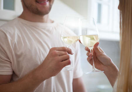 Happy young couple enjoying a glass of white wine at the kitchen photo