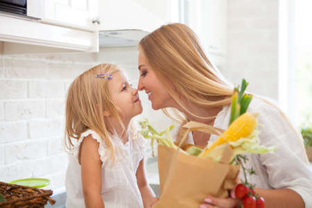 Young happy woman with her daughter cooking in a modern kitchen setting Stock Photo