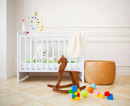 Lege kinderkamer met mand, speelgoed en houten paard Stockfoto