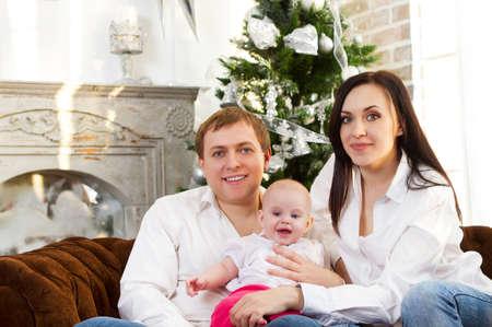 baby near christmas tree: Happy smiling family with baby near the Christmas tree Stock Photo