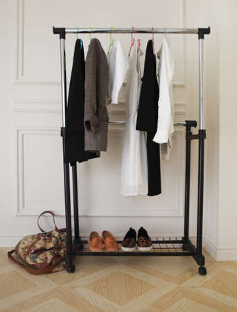 Female black and white clothes on a rod, shoes and bag on a wooden floor photo