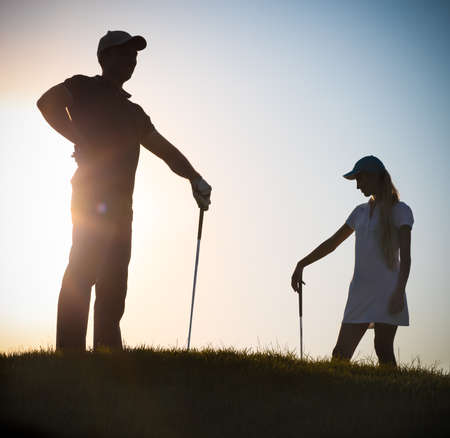 Male and female golfers playing golf at sunset photo