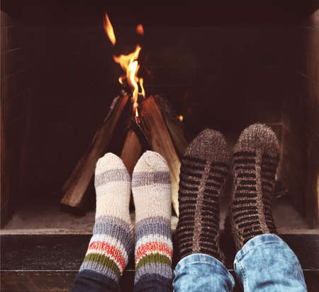 fireplace family: Close up of romantic legs of a couple in socks in front of fireplace at winter season at home