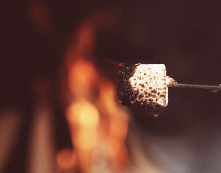 Close up of a marshmallow on a stick being roasted over a fire Stock Photo
