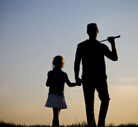 Father and his daughter playing golf at sunset photo