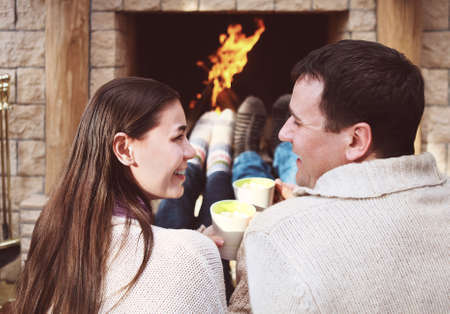 home keeping: Couple holding cups with hot chocolate with marshmallows in front of lit fireplace Stock Photo