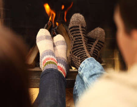 Close up of romantic legs of a couple in socks in front of fireplace at winter season at home photo
