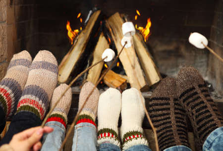 Feet of the family warming at a fireplace with marshmallows on sticks