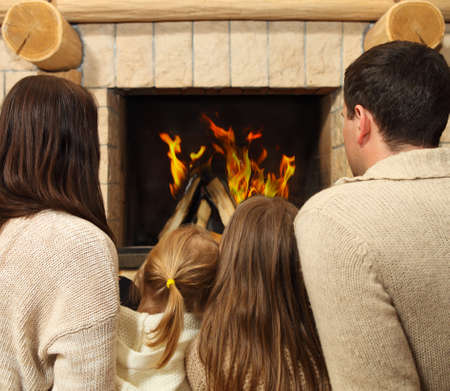Young happy mother, father and two daughters by a fireplace on Christmas