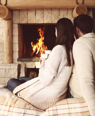 Couple tenant des tasses de chocolat chaud avec des guimauves devant un feu de foyer Banque d'images