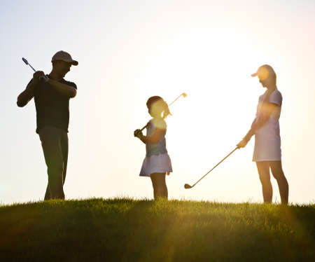 Family of a golfers playing golf at sunset photo