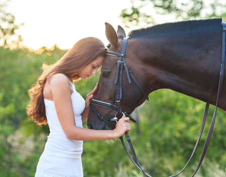 caresses: Portrait beautiful woman with long hair next horse. Focus on the horse