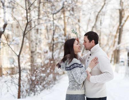 muerdago: Feliz pareja de j�venes bajo el mu�rdago se divierten en el parque de invierno