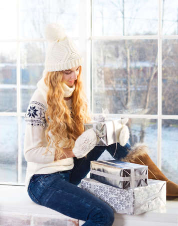 winter window: Young happy blond woman in white hat looking at Christmas presents sitting by the window Stock Photo
