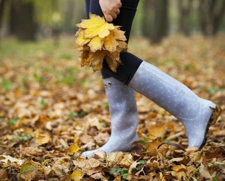botas de lluvia: Mujer que se divierten con hojas de arce amarillas en el parque de otoño
