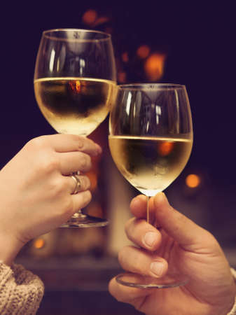 indoor: Romantic young couple toasting wineglasses in front of lit fireplace Stock Photo
