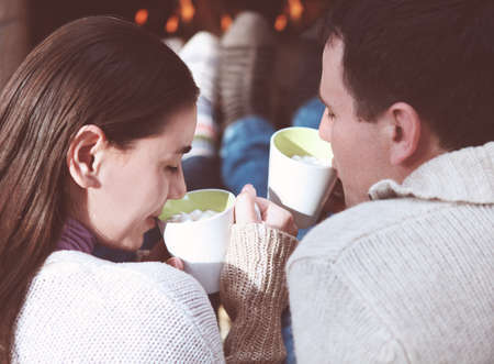 hot chocolate drink: Close-up of couple holding cups with hot chocolate with marshmallows in front of lit fireplace