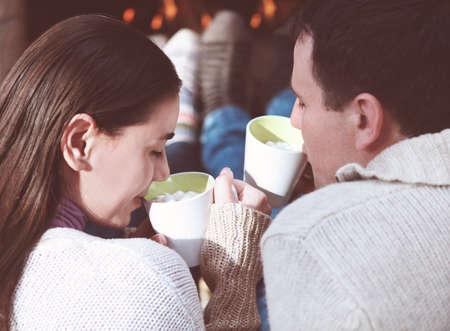 chocolate caliente: Primer plano de la pareja la tazas de chocolate caliente con malvaviscos en frente de la chimenea encendida