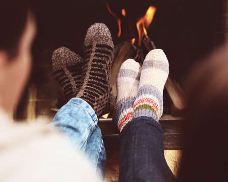 home keeping: Close up of romantic legs of a couple in socks in front of fireplace at winter season at home